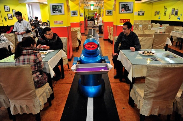 A 'waiter' robot holds an empty tray after serving meals to the customers