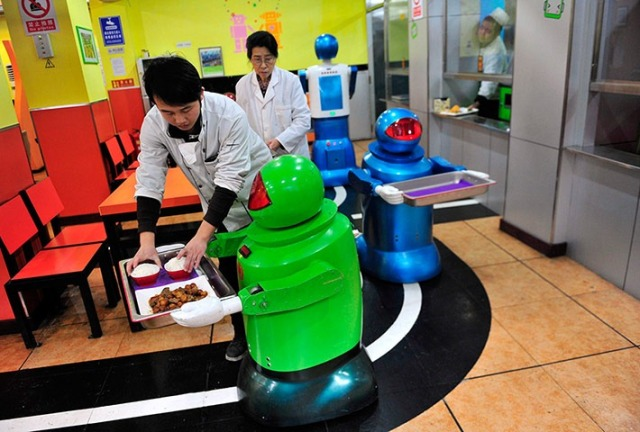 Human waiters assist the robots in loading the trays of food